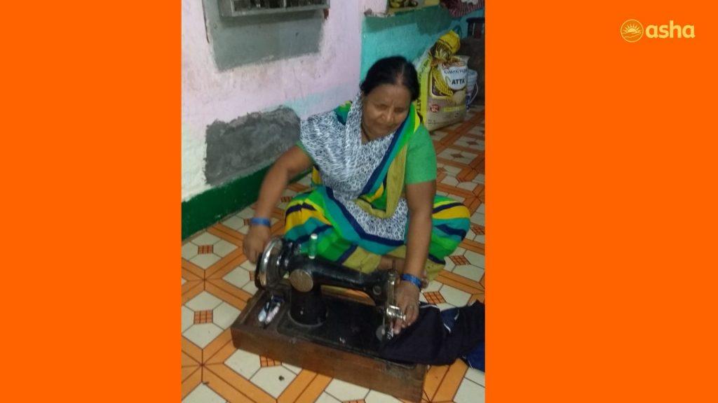 Kamla stitching clothes in her shanty in Asha's Anna Nagar slum community