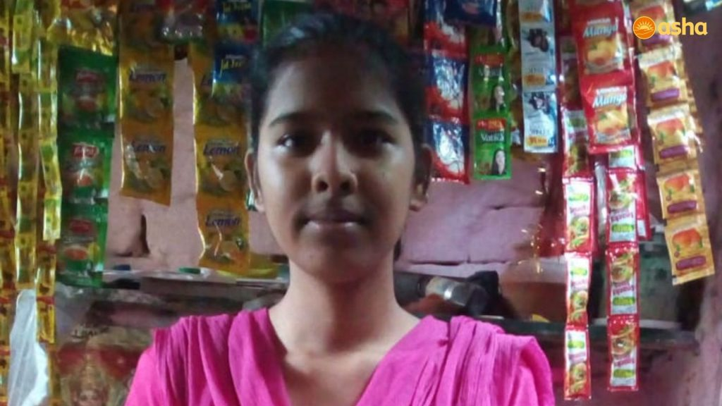 Shivani in front of her father's shop in Udhyog Nagar, Tanki No.2 near Asha's Punjabi Bagh slum community